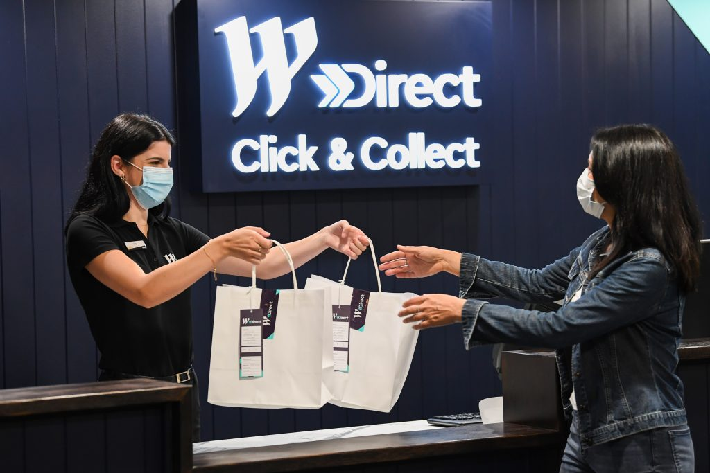 Two women where masks, one woman is receiving her purchases
